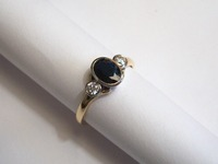 18ct yellow and white gold three stone ring set with oval cut sapphire and diamonds in a rubover setting