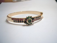 9ct yellow gold hinge bangle set with emeralds, blue sapphires and rubies taken from old jewellery supplied by the customer