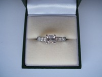 18ct white gold ring set with Asscher cut centre stone and princess cut diamonds on the shoulders