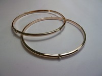 Set of two simple red gold slave bangles with white gold detail